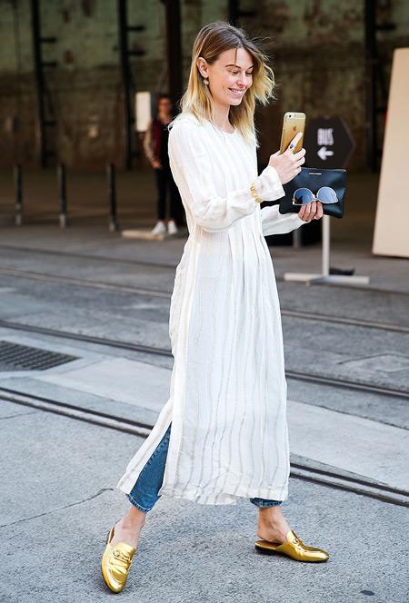 Модель в джинсах, белое легкое платье, золотые сандалии