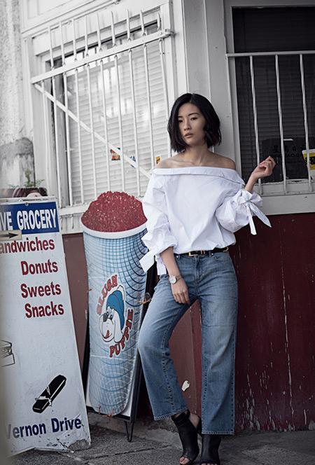 Модель в джинсах прямого покроя, белая блузка, ботильоны с открытой пяткой и носком