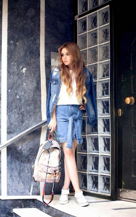 Модель в джинсовой юбке, белый топ и кеды