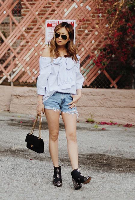 Модель в джинсовых шортах, голубой рубашке, черные ботильоны и сумочка