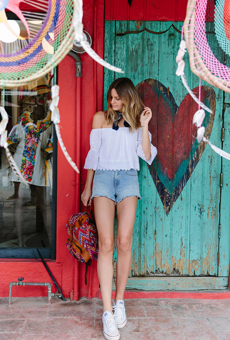 Модель в голубых шортах, белая блуза с открытими плечами, кеды