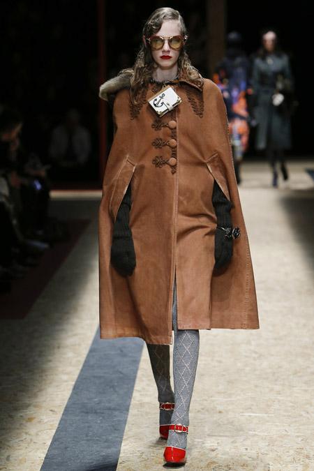 Модель в коричневом пальто с выемками для рук от Prada - модные пальто осень 2016, зима 2017