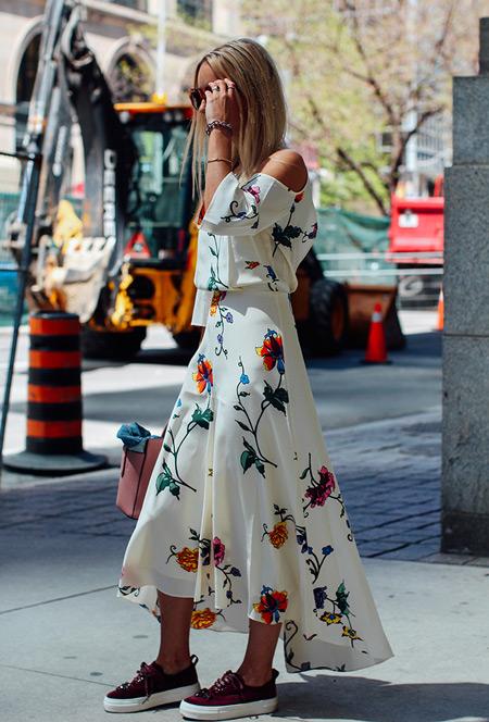 Модель в красивом белом платье с цветами и бордовых кедах на белой платформе