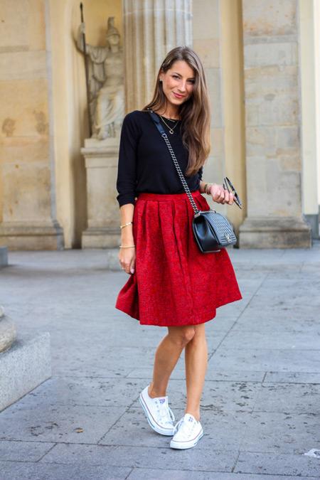 Модель в красной юбке, черной блузе и белых кедах