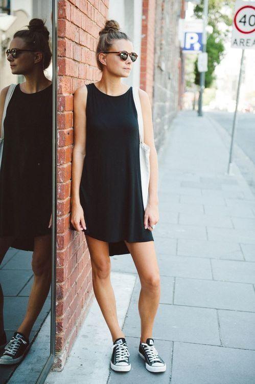 Модель в легком черном платье без рукавов, кеды