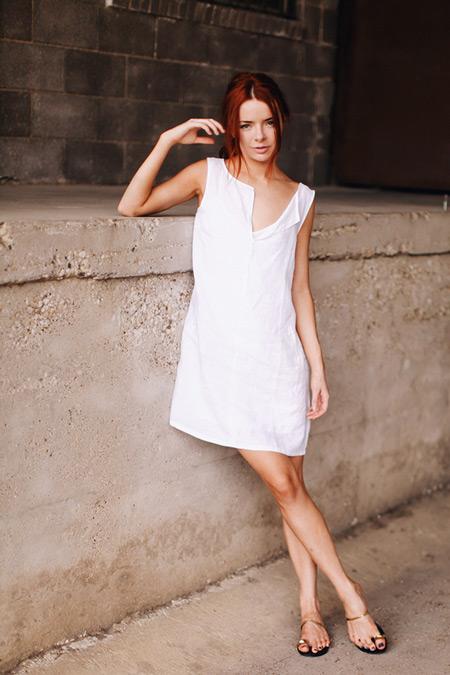 Модель в летнем белом платье и сандалиях