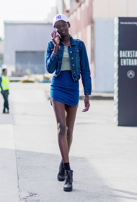 Модель в мини юбке, джинсовке, светлый топ, ботинки на шнурках и кепка