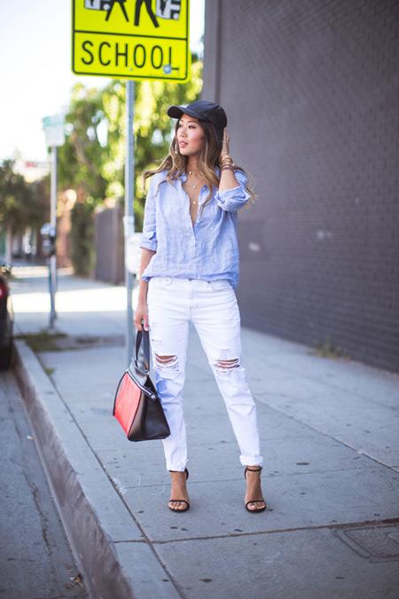 Модель в рванных белых джинсах, голубая рубашка и черные босоножки