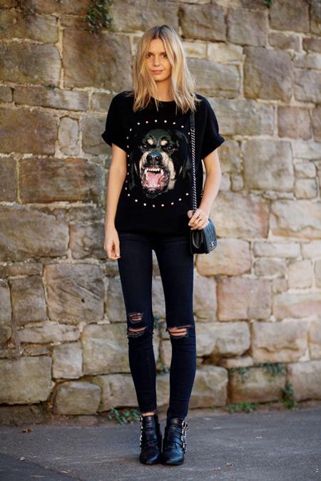 Модель в рваных черных джинсах и футболке с рисунком