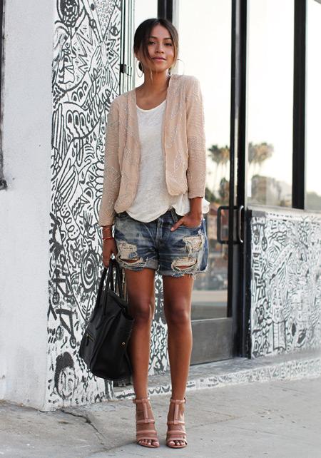 Модель в рваных джинсовых шортах, белый топ и светлая кофточка, босоножки