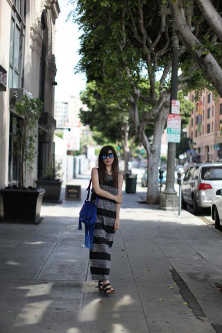 Модель в серо-черном длинном сарафане без рукавов, синяя сумка с бахромой