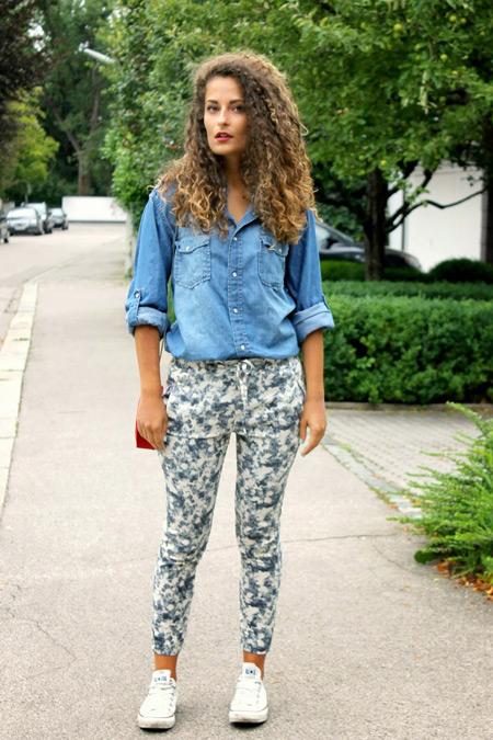 Модель в серых штанах и джинсовой рубашке, белые кеды