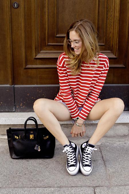 Модель в шортах, красный свиошот с полосками и черно-белые кеды