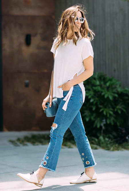 Модель в укороченных джинсах и белой футболке