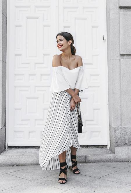 Девушка в белом кроп топе и светлой полосатой юбке, черные босоножки