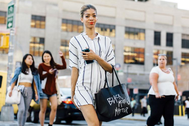 Девушка в белом платье рубашка и черная сумка тоут с надписью