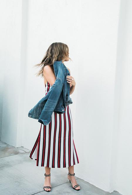 Девушка в белом платье с красно черную вертикальную полоску и джинсовая куртка