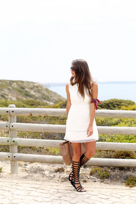 Девушка в белом сарафане и черные сандалии гладиаторы