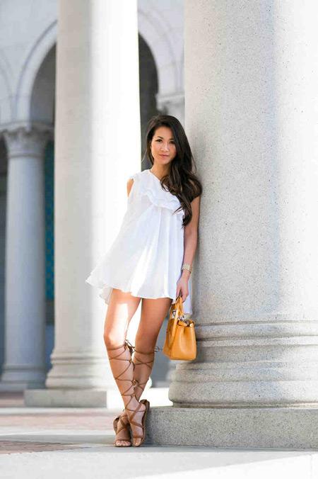 Девушка в белом сарафане и сандалии гладиаторы на плоской подошве