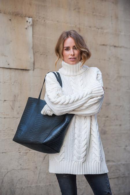 Девушка в белой кофте, джинсах и с черной сумкой тоут