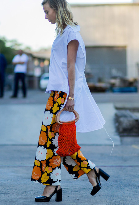 Девушка в белой рубашке и брюках клеш с ярким принтом