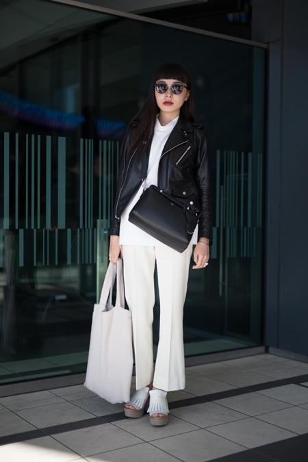 Девушка в белых брюках, куртка косуха и белая сумка тоут