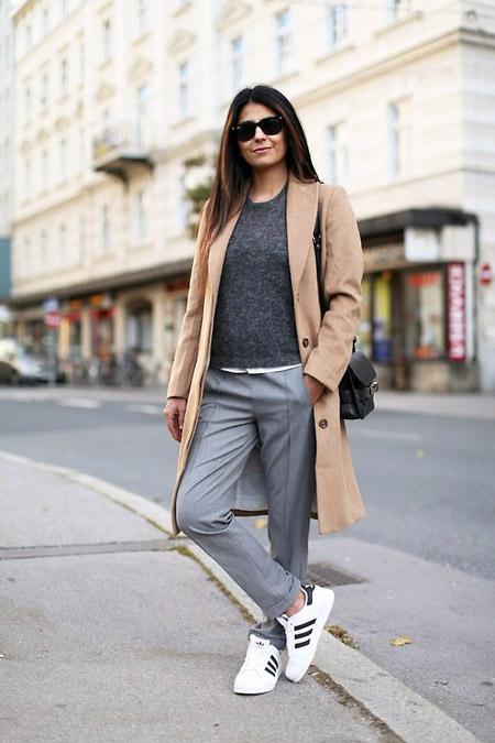 Девушка в белых кроссовках и пальто