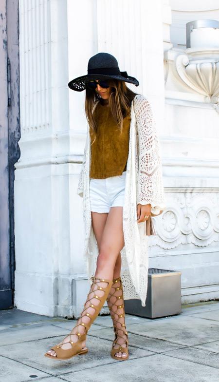 Девушка в белых шортах, кардиган, черная шляпа и сандалии гладиатора