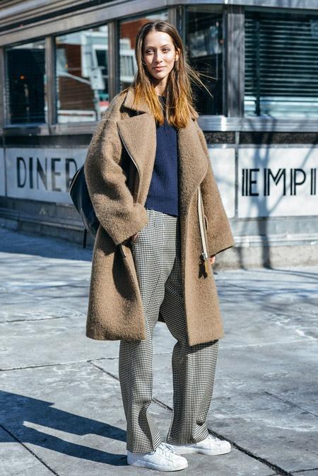 Девушка в бежевом пальто и белых кроссовках