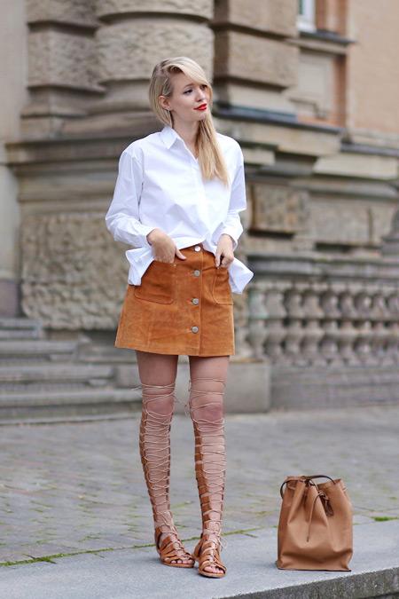 Девушка в бежевой юбке на пуговицах, белая рубашка и сандалии гладиаторы