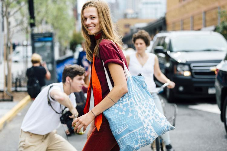 Девушка в бордовой футболке, джинсы и голубая сумка тоут