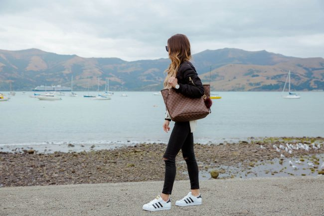 Девушка в черном бомбере, белых кроссовках и сумкой тоут