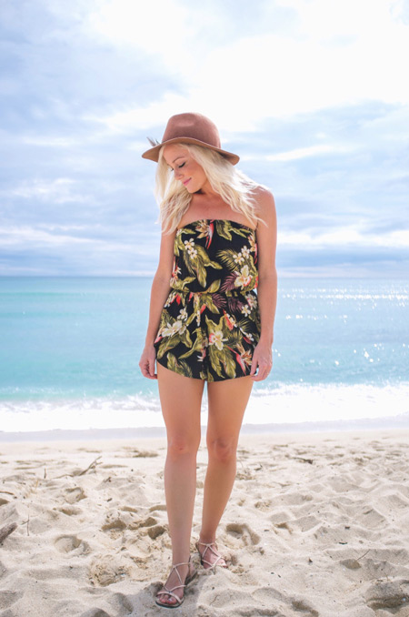 Девушка в черном комбинезоне с тропическим принтом, шляпа