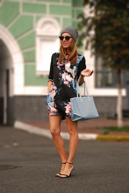 Девушка в черном платье, босоножках и шапочке