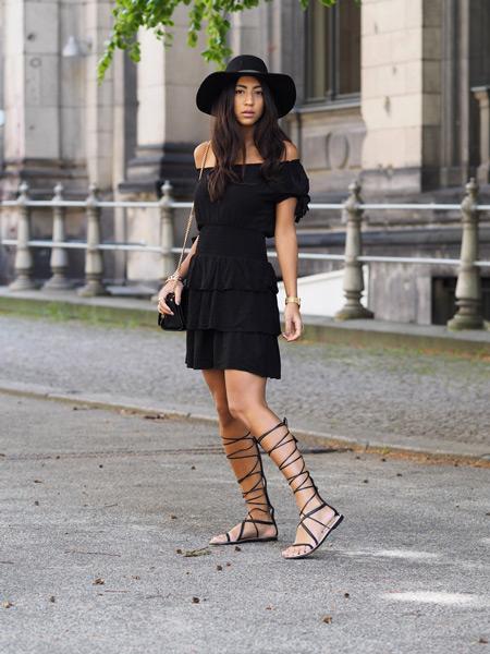 Девушка в черном платье с рюшами, шляпа и сандалии гладиаторы