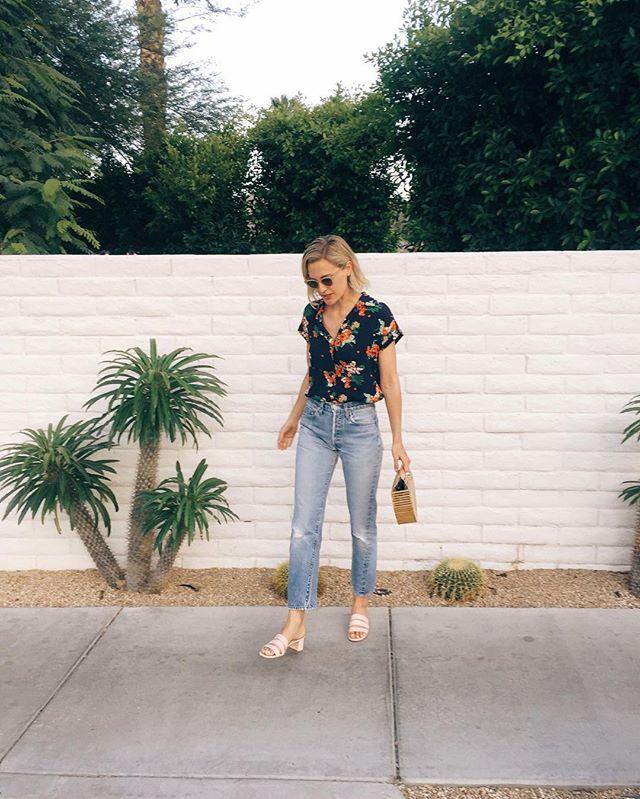 Девушка в черной блузе с принтом и укороченных джинсах