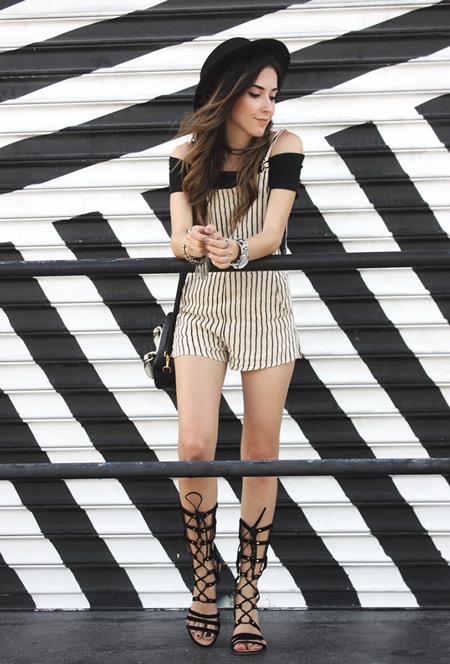 Девушка в черной футболке, полосатый комбинезон и черные сандалии гладиаторы