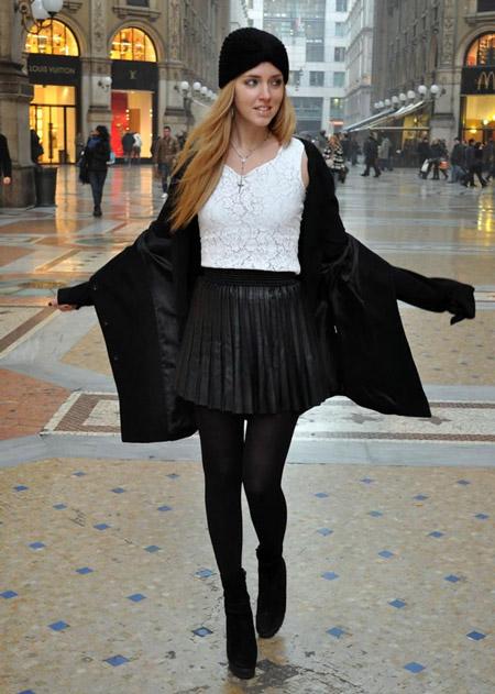 Девушка в черной кожаной юбке и шапке