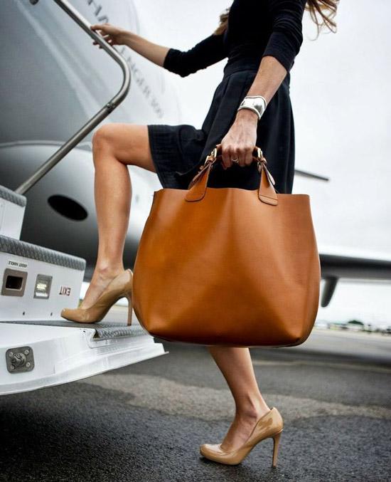 Девушка в черной юбке, джемпере и с коричневой сумкой тоут