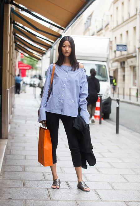 Девушка в черных бриджах и голубой рубашке в тонкую полоску