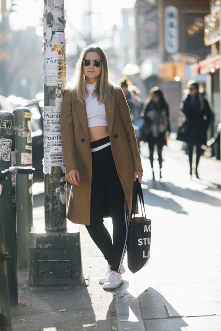 Девушка в черных штанах, белый кроп топ и черная сумка тоут