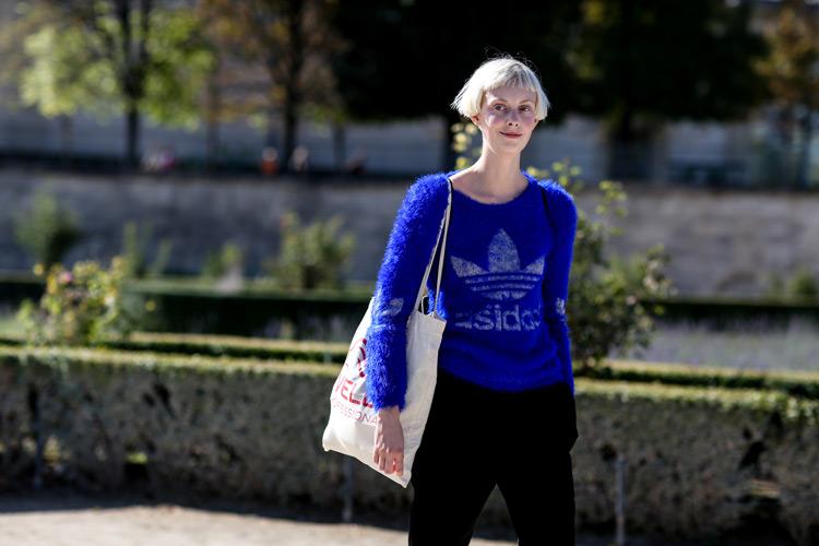 Девушка в черных штнах, синяя кофта и белая сумка тоут