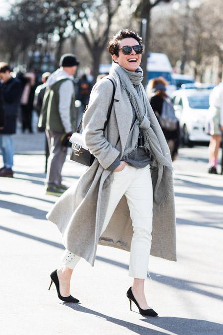 Девушка в длинном пальто и белых брюках