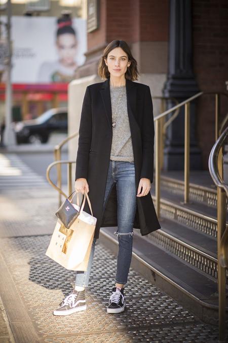 Девушка в джинсах, серый джемпер, черное пальто и бежевая сумка тоут