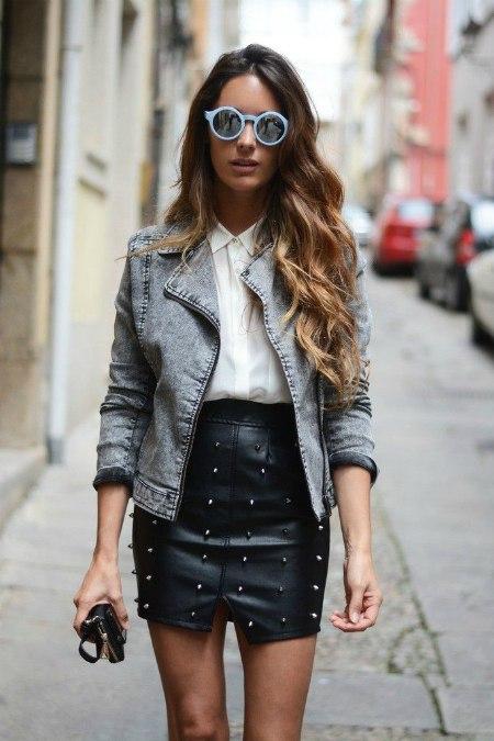Девушка в джинсовой куртке и кожаной юбке