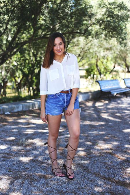Девушка в джинсовых шортах, белая блуза и черные сандалии гладиатора