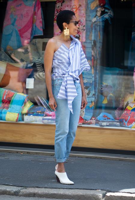 Девушка в голубых джинсах и ассиметричной блузе с голубой полоской
