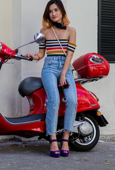 Девушка в голубых джинсах и разноцветном полосатом топе