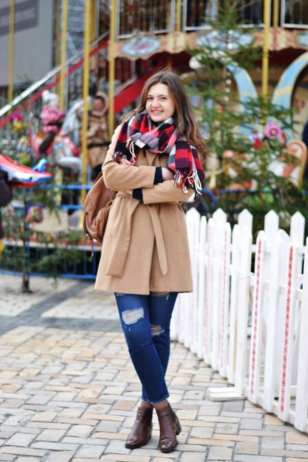 Девушка в клетчатом шарфе и бежевом пальто