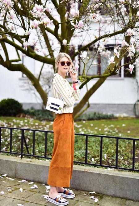 Девушка в коричневых широких брюках, белая рубашка в бежевую полоску и сланцы на платформе
